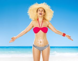Perfect summer. smiling active woman on the seashore with sun drawn by spf creme on the stomach