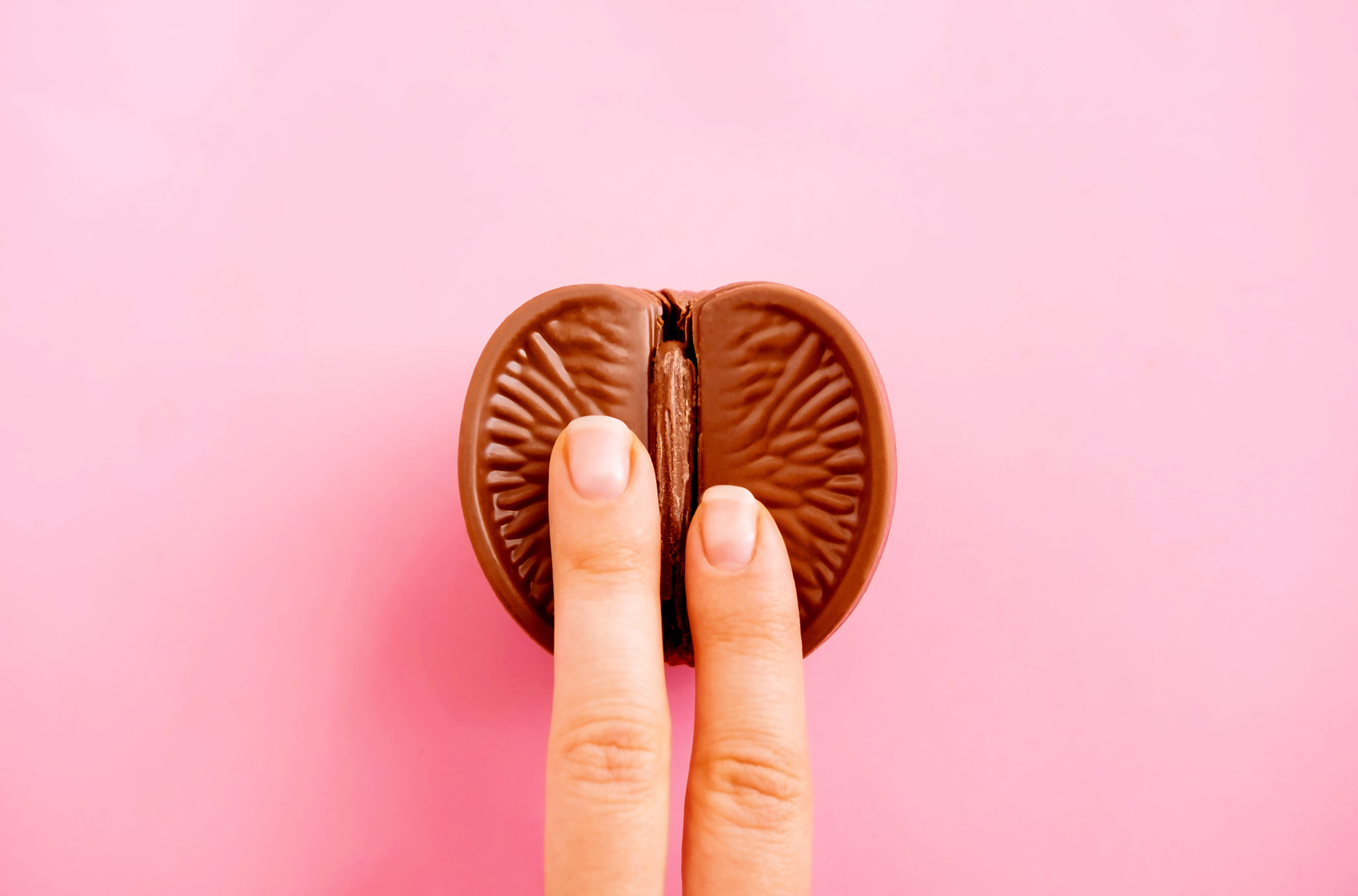 Vagina symbol. Two fingers on chocolate orange on pink background. Sex concept. Top view, copy space